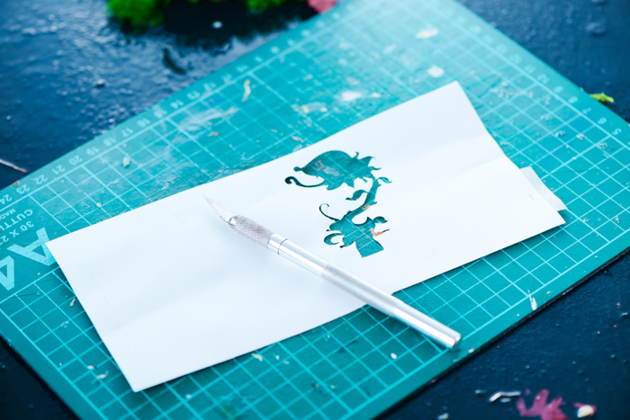 a cut out silhouette of a flower in a piece of paper on a cutting mat
