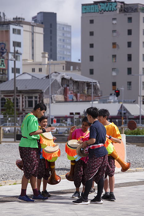 candid street photo of a group of children drumming outdoors