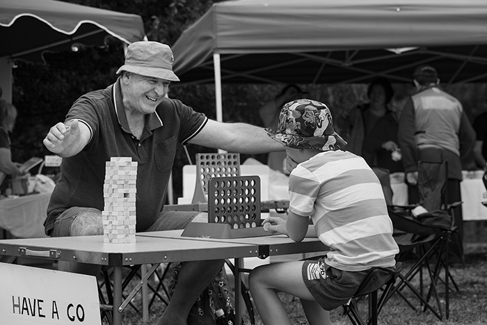 candid street photo of a father and son playing connect four outdoors