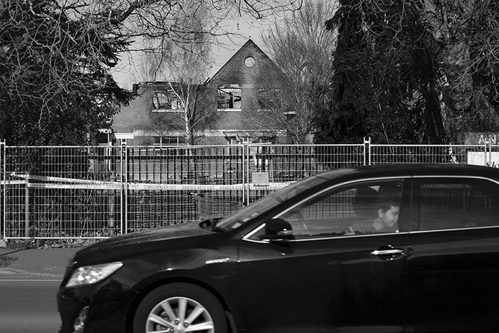 candid street photography of a car driving by an old building