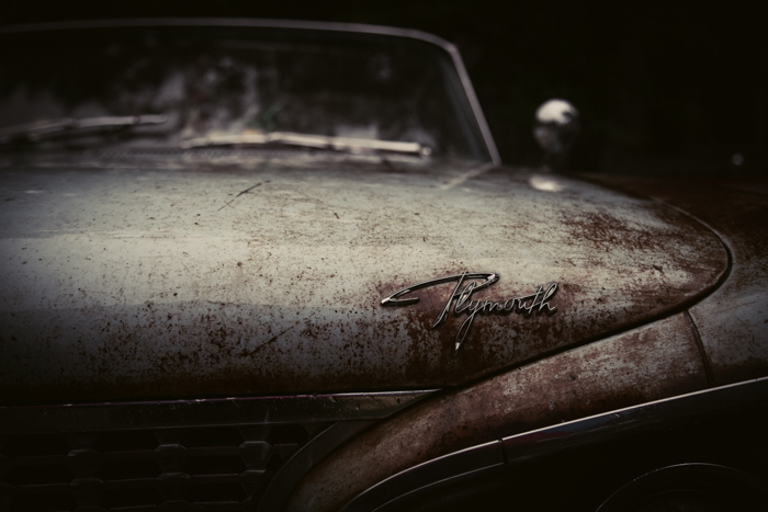 the front of a rusty plymouth car