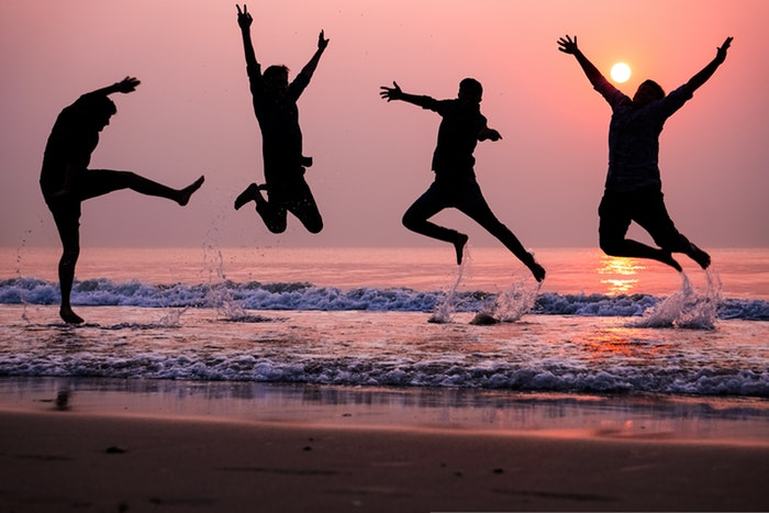 the silhouettes of four people jumping with joy on a beach at sunset, utilizing dynamic range in photography