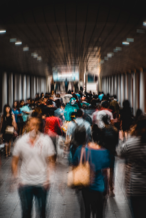 blurry street photo of a group of people walking through a subway station - focus breathing