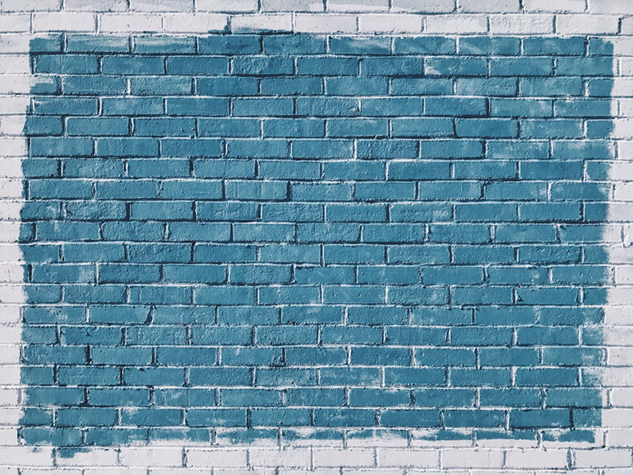 A textured brick wall painted blue and white - composition geometry