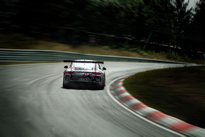a race car speeding on a race track featuring motion blur photography