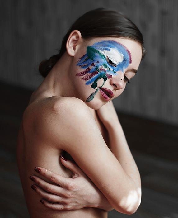 Artistic nude photography of a female model with paint on her face