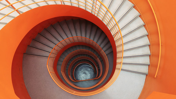 overhead shot of a winding orange staircase - symbolism in photography