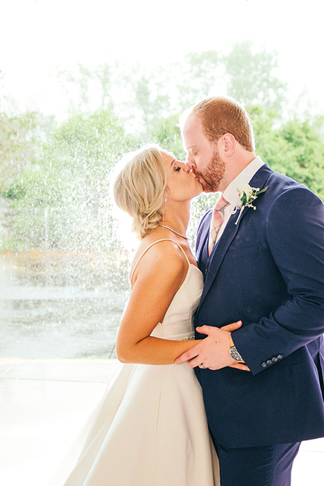 portrait of the newlyweds kissing at an outdoor wedding photography shoot
