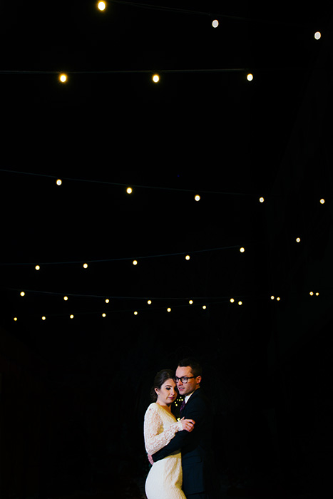 portrait of the newlyweds dancing at an outdoor wedding at night