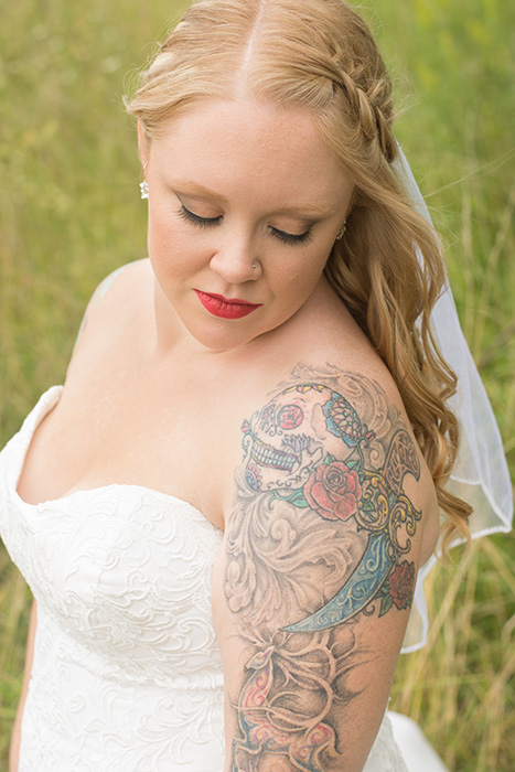 A close up outdoor wedding photography portrait of a tattooed bride