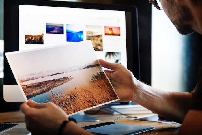 a photographer editing landscape images in a home office