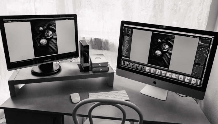a photographers home office with two laptop screens open on an editing program showing how to print photos professionally