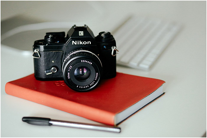 a Nikon camera resting on a red notebook - portrait photography pricing
