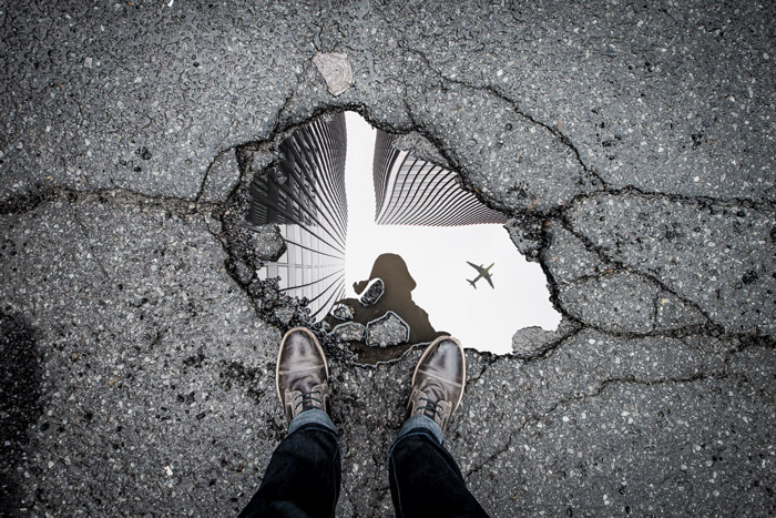 a photographers shoes and reflection in a puddle - symbolism in photography