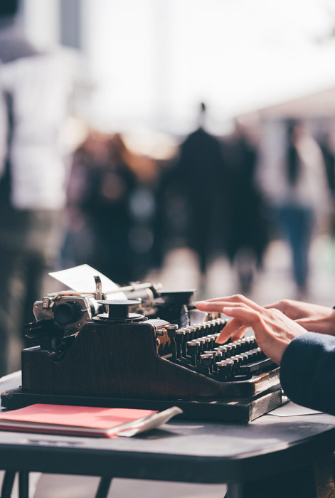 a person typing on a vintage typewriter - symbolism in photography