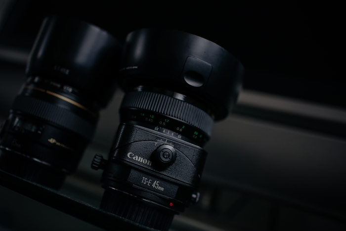 two canon lenses on a shelf, focused on the Canon lens abbreviations