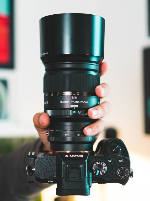a photographer holding a Sony DSLR with a constant aperture lens