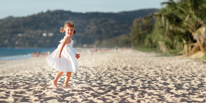 a little girl running on the beach, her action frozen in motion