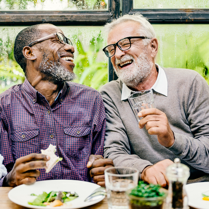 portrait of two male friends laughing over dinner