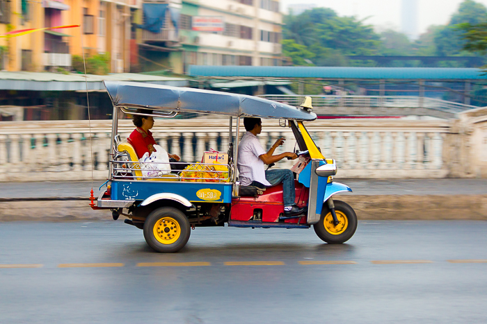 A freeze motion photography shot of a colorful tuktuk racing through the city