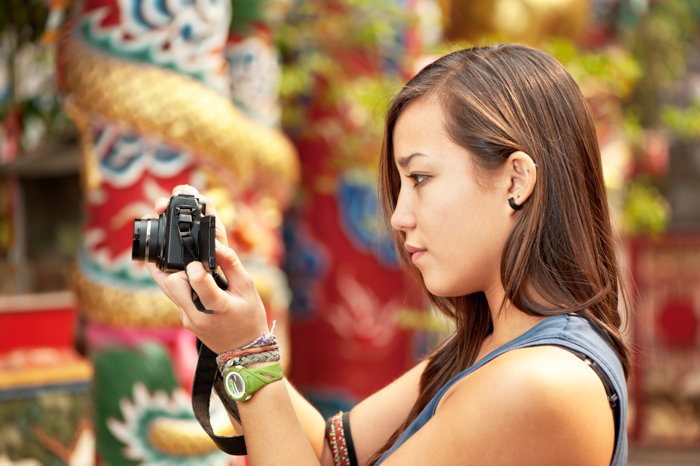 Photo of a woman checking the settings of her camera
