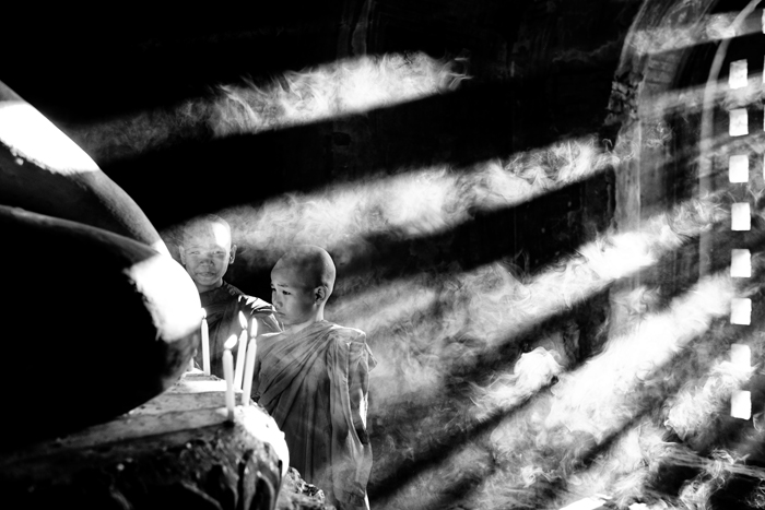 Atmospheric monochrome shot of young monks lighting candles with incident light shining through a doorway
