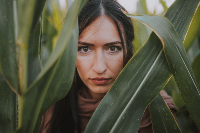 A woman with brown eyes looking through tall leaves