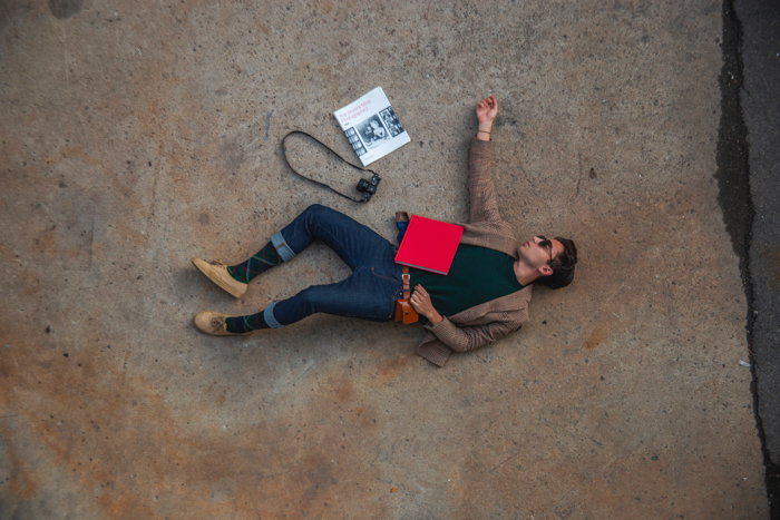 Man lying on floor with camera and notebook