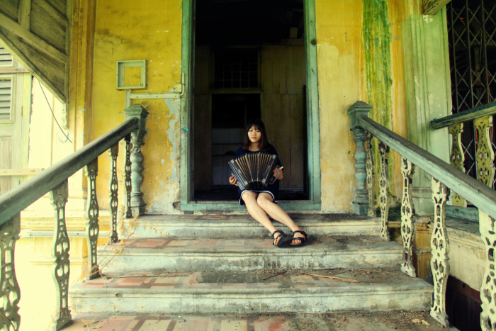 Photo of a girl playing the accordion on the stairs of an abandoned house