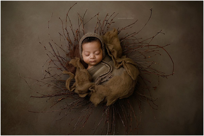 Artistic photo of a baby in front of a brown background