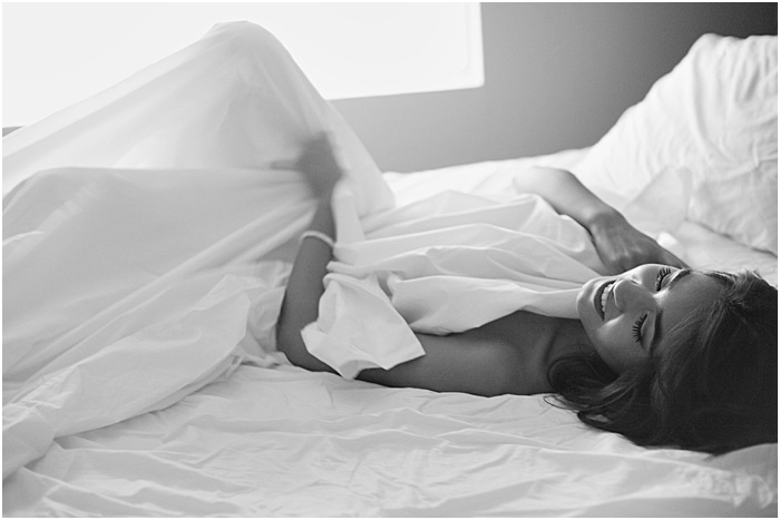 Black and white photo of a woman lying between white sheets