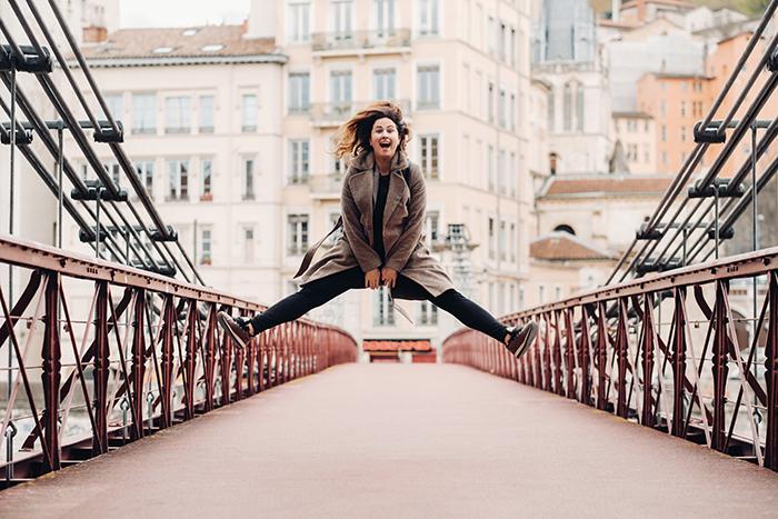 Girl jumps on a symmetrical bridge.
