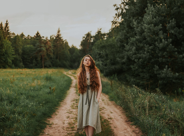 Photo of a red-haired girl in the middle of a dirt road on a field
