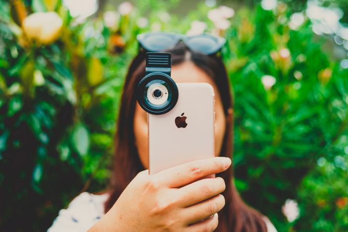 Photo of a girl holding her iPhone in frontof her face to take a photo