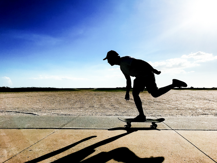 Photo of a skateboarding man in movement with blue sky background