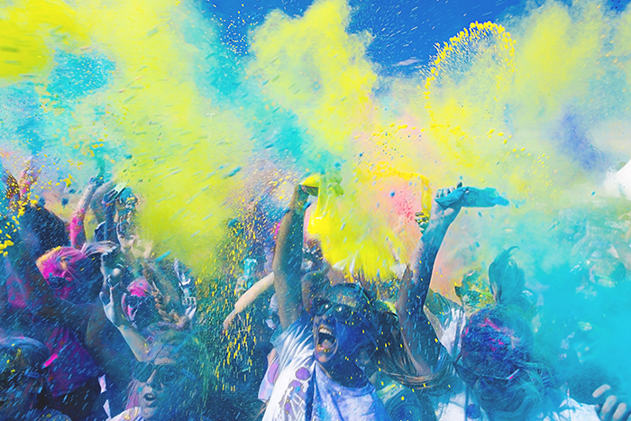 Photo of a crowd at a festival with yellow and blue colour powder thrown in the air