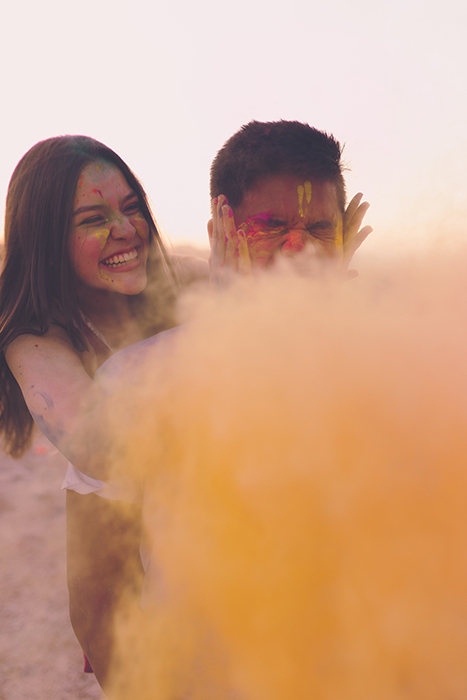Photo of a girl and a boy with simple background behind yellow color powder