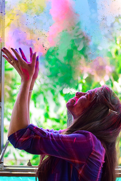 Side-view photo of agirl throwing rainbow colour powder in the air, fast shutter speed