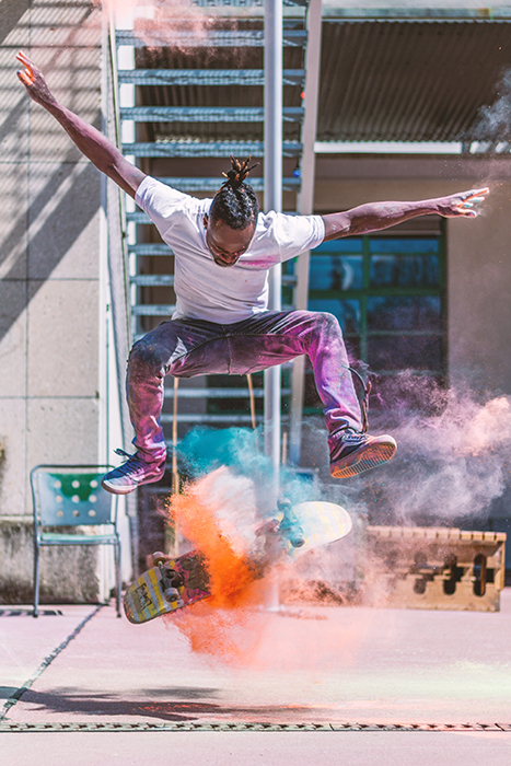 Photo of a man doing a skateboarding trick with orange color powder