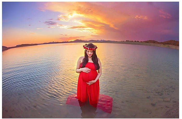 Photo of a pregnant woman standing in the water at sunset