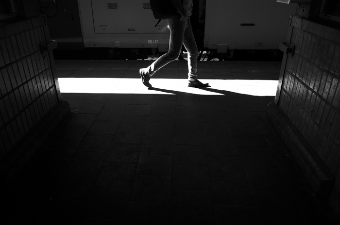 Black and white image showing a persons legs walking along a lit corridor