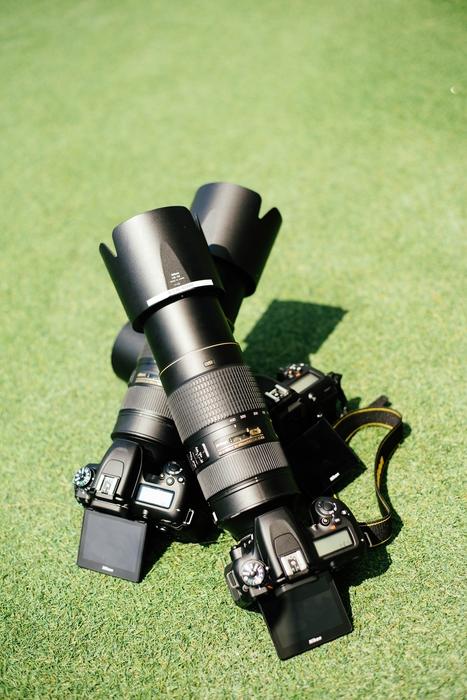 two nikon telephoto lenses on grass