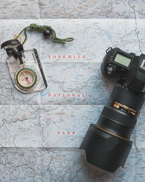a nikon camera with zoom lens resting on a map
