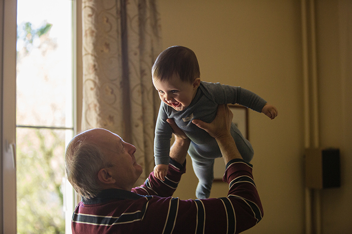 cute family portrait of a granddad playing with grandson