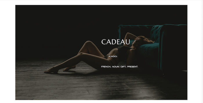 Boudoir photo of a model in front of a green sofa by Cadeau