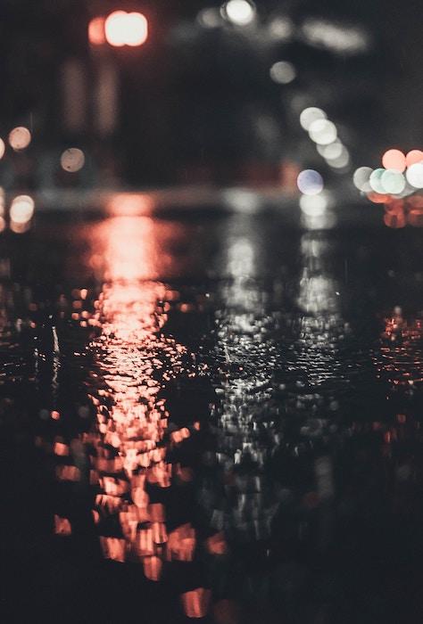 Photo of reflecting light on wet pavement