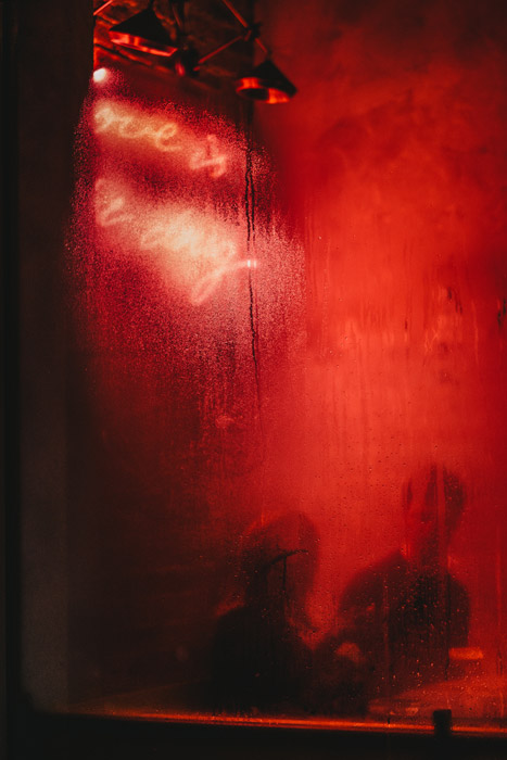 Photo of a bar with red light reflecting on the window