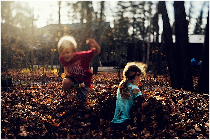 Photo of children playing with autumn leaves