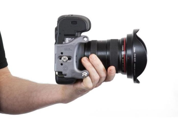 a photographer holding a DSLR showing the underneath of the camera body