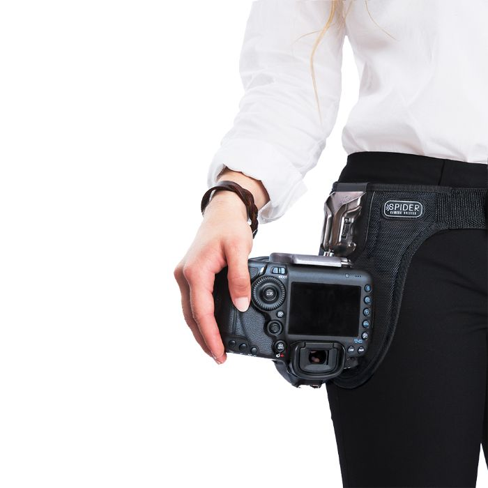 A photographer wearing a SpiderPro Single Camera System v2 with a DSLR camera attached